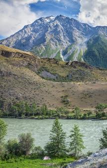 Berglandschaft an einem sommertag, fluss und felsigem gipfel