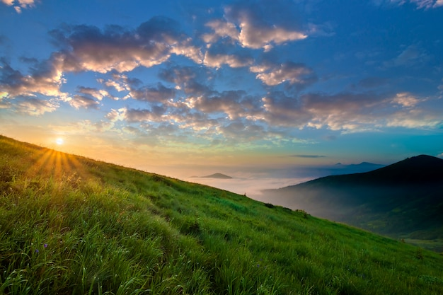 Berglandschaft bei schönem wetter bei sonnenaufgang. grüner grasartiger steiler hügel, nebeliges tal und entfernte berge unter hellem blauem himmel mit beleuchtet, indem man weiße wolken der sonne anhebt. schönheit des naturkonzeptes.