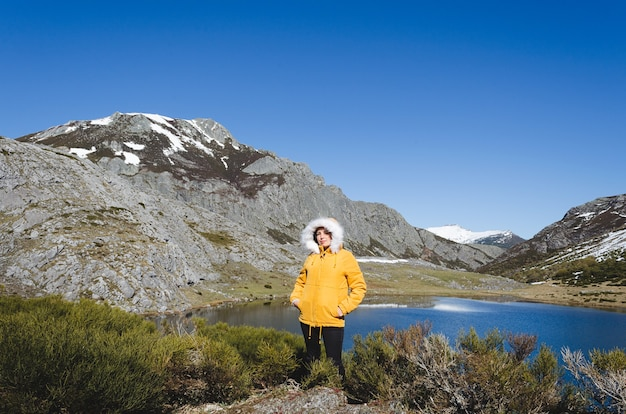 Berglandschaft mit schneebedeckten bergen und see. frau in der gelben jacke, die kamera betrachtet. see isoba, leon. spanien.