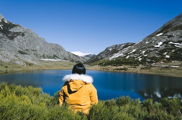 Berglandschaft mit schneebedeckten bergen und see. frau mit gelbem mantel, der den see betrachtet. see isoba, leon. spanien.