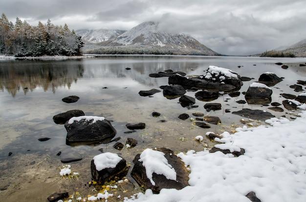 Bergsee froliha, kiefer und steine mit schnee am spiegelsee