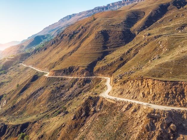 Bergserpentin im morgensonnenlicht. gefährliche schmale unbefestigte bergstraße durch die hügel zu einem hochgelegenen dorf. luftaufnahme.