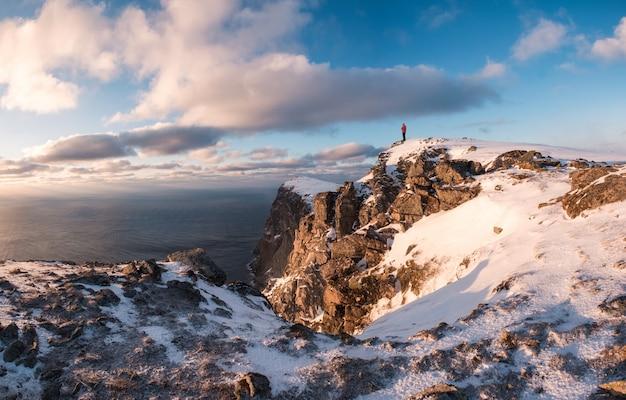 Bergsteiger, der auf spitze des felsenberges im winter bei sonnenuntergang steht