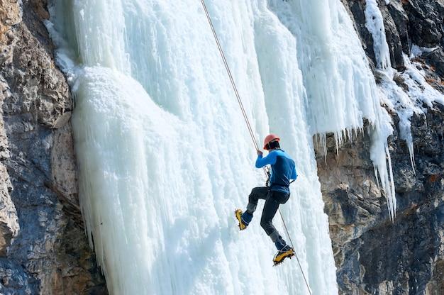 Bergsteiger, der das seil mit einem gefrorenen wasserfall hinuntergeht