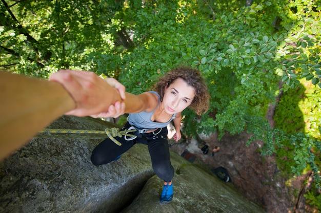 Bergsteiger, der weiblichem bergsteiger hilft, eine spitze des berges zu erreichen