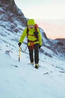 Bergsteiger klettert auf einen schneeberg