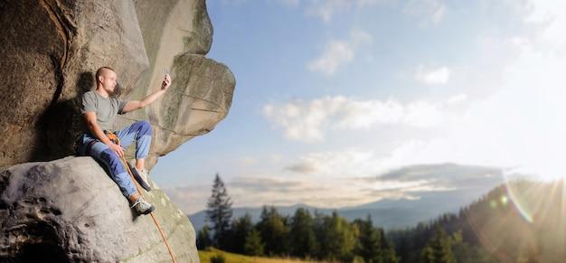Bergsteiger sitzt auf dem großen natürlichen flussstein, der mit dem seil gegen blauen himmel und berge gesichert wird