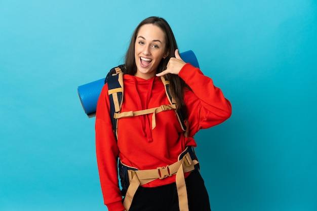 Bergsteigerfrau mit einem großen rucksack über lokalisiertem hintergrund, der telefongeste macht. rufen sie mich zurück zeichen