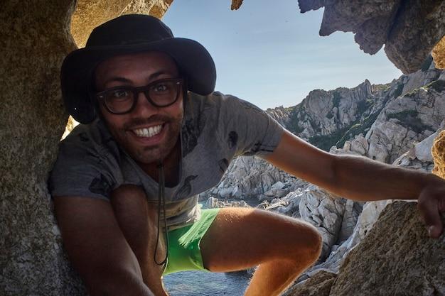 Bergsteigerjunge auf den felsen in sardinien während des sonnenuntergangs