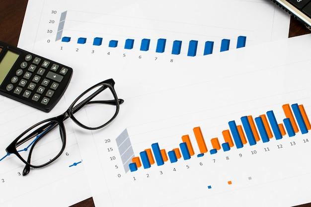 Bericht vorbereiten. blaue grafiken und diagramme. geschäftsberichte und stapel von dokumenten auf holztisch