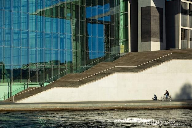 Berlin - deutschland - dcember 2018. ein mann auf einem fahrrad fährt in der nähe von marie-elisabeth-lueders-haus - modernes gebäude im bezirk mitte ist teil des bundestages.