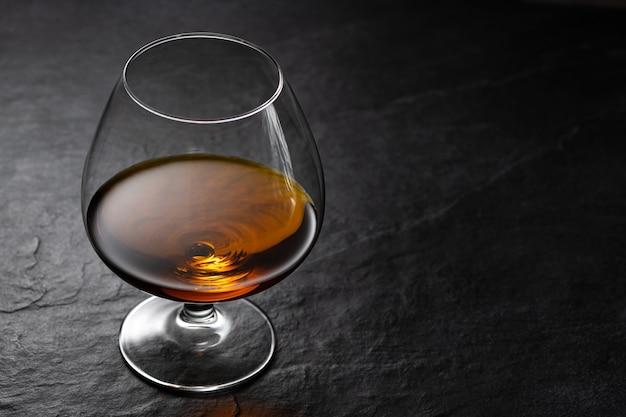 Bernsteinbrand in cognacglas auf schwarzem steintisch mit studioreflexion