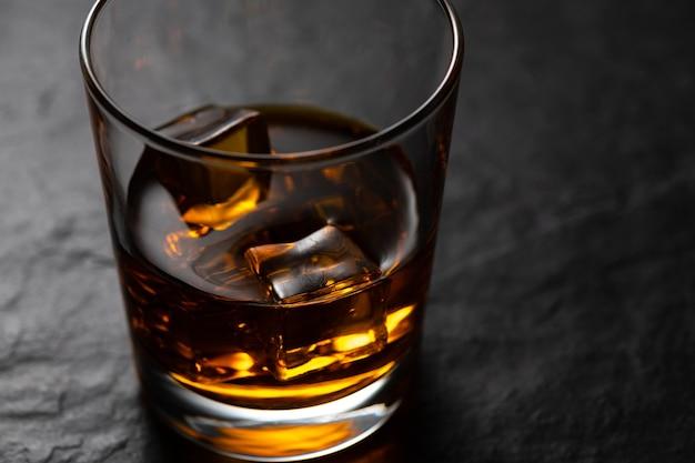 Bernsteinfarbener whisky mit eiswürfeln im alten modeglas auf schwarzem steintisch mit studioreflexion. nahaufnahme