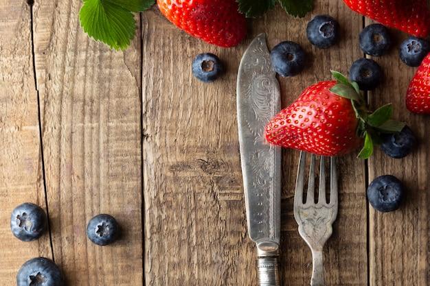 Berriey-mischung, blaubeere, erdbeere auf hölzernem hintergrund mit weinlese, angeredeter gabel und messer.