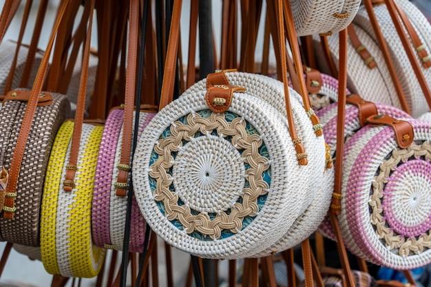 Berühmte balinesische rattan-öko-taschen in einem lokalen souvenirmarkt auf der straße in ubud, bali, indonesien. kunsthandwerk und souvenirladen, nahaufnahme