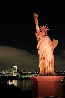 Berühmte historische freiheitsstatue, die den nachthimmel in odaiba, tokio, japan berührt