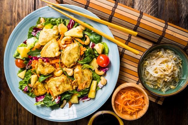 Berühmte thailändische küche mit bohnen sprießen und salat auf tischset