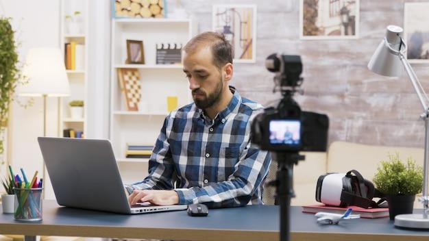 Berühmter junger vlogger, der auf einem laptop tippt, während er mit seinen abonnenten in einem podcast spricht. kreativer inhaltsersteller.
