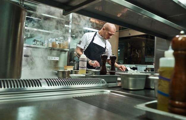 Berühmter koch in schwarzer schürze, der in einer restaurantküche arbeitet. food-konzept