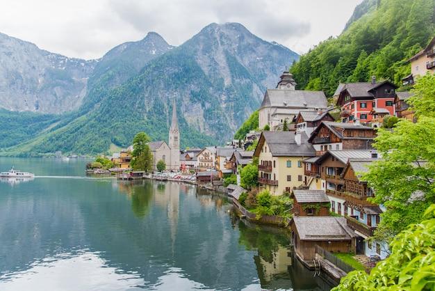 Berühmtes hallstatt-bergdorf in den österreichischen alpen mit passagierschiff