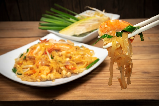 Berühmtes thailändisches lebensmittel nannte die auflage, die auf weißer platte thailändisch ist