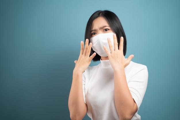 Berühre dein gesicht nicht. asiatische frau, die hygienemaske trägt, die handstoppschild und stehend zeigt
