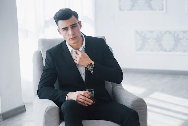 Berührt den kragen. junger eleganter kerl im schwarzen anzug sitzt auf weißem stuhl und hält glas mit alkohol.