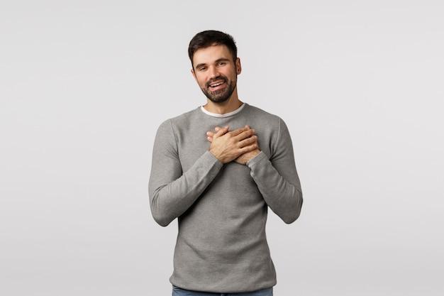 Berührt und zu tränen gerührt, charmant, bärtiger mann in grauem pullover, hände zu herzen drücken, vor bewunderung und versuchung seufzen, entzückt lächeln, lob erhalten, sich dankbar und herzerwärmend fühlen