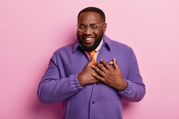 Berührter fröhlicher bärtiger schwarzer mann hört herzerwärmende worte, drückt freundlichkeit aus, trägt transparente brille, trägt optische brille, lila jacke