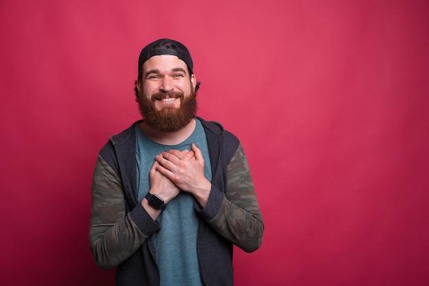 Berührter großer bärtiger hipster hält hände an seiner brust