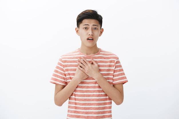 Berührter und entzückter empfindlicher junger asiatischer teenager, der augenbrauen hochzieht