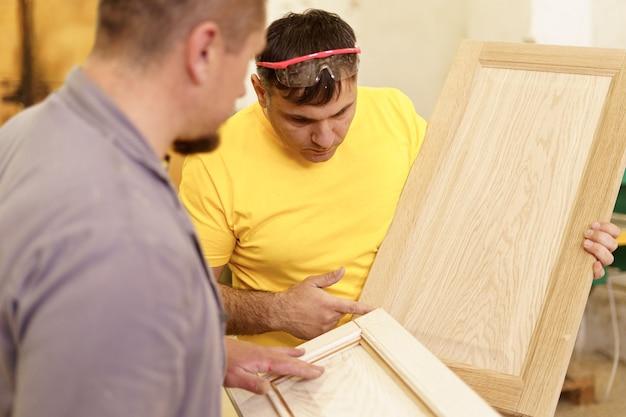 Beruf, tischlerei, holzarbeiten und menschenkonzept - zwei tischlerarbeiten mit holz für möbel in der werkstatt.