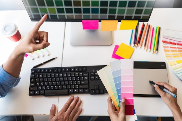 Beruflicher grafiker des kreativen architekten, der die farbpalettenbeispiele für das projekt auf büro-desktop-computer auswählt