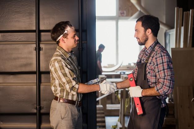 Berufs-, technologie- und personenkonzept - zwei arbeiter mit tablet-pc in der werkstatt