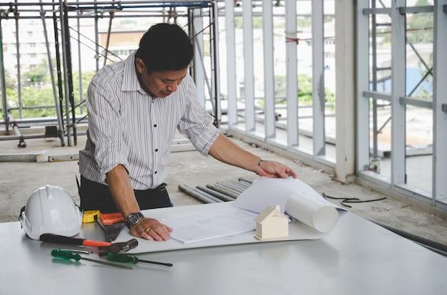 Berufsarchitekt, ingenieur oder innenzeichnung mit plan und werkzeugen auf konferenztisch in der büromitte auf baustelle,