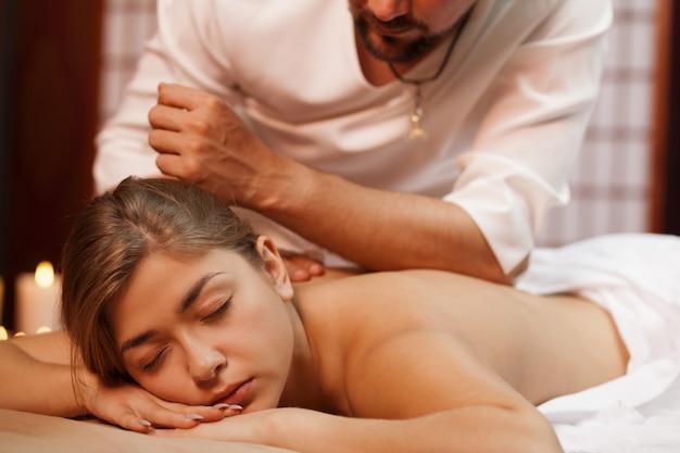 Berufsbadekurorttherapeut, der seinem weiblichen kunden entspannende rückenmassage gibt. schönheit, die traditionelle massagetherapie in der badekurortmitte genießt. attraktive frau, die an der schönheitsklinik sich entspannt