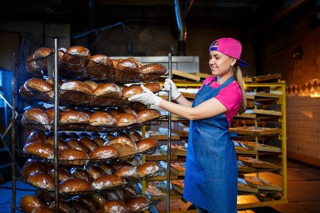 Berufsbäcker - eine junge hübsche frau in einer jeansschürze hält frisches brot in ihren händen. bäckereiprodukte. brotproduktion