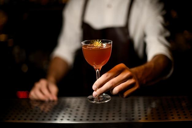 Berufsbarmixer, der ein cocktail im glas mit einer kleinen gelben blume dient