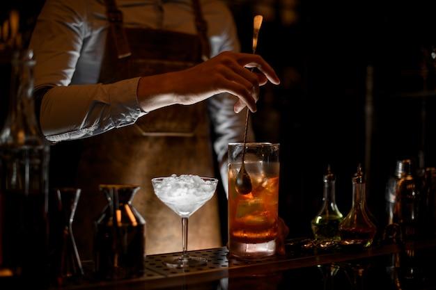 Berufsbarmixer, der ein cocktail in der messenden glasschale rührt
