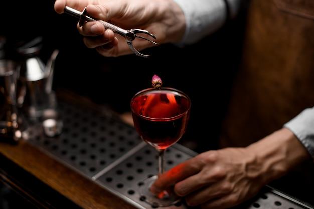 Berufsbarmixer, der eine kleine rosenknospe zum roten cocktail in das glas einsetzt