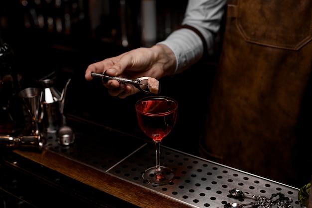 Berufsbarmixer, der eine rosenknospe zum roten cocktail in das glas einsetzt
