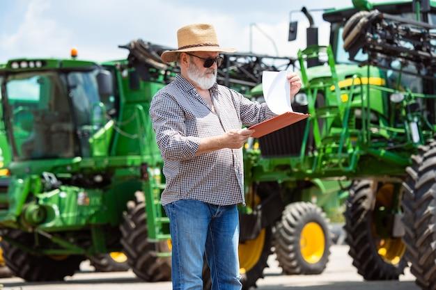 Berufsbauer mit einem modernen traktor bei der arbeit mit dokumenten. sieht sonnenschein aus. landwirtschaft, ausstellung, maschinen, pflanzenbau. älterer mann in der nähe seiner maschine.