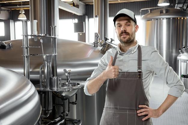 Berufsbrauer in eigener handwerklicher alkoholproduktion. spezialist, mann in arbeitskleidung posiert selbstbewusst mit daumen nach oben. konzept des offenen geschäfts, ökoprodukt, handwerksbrauerei, individuelle fabrik.