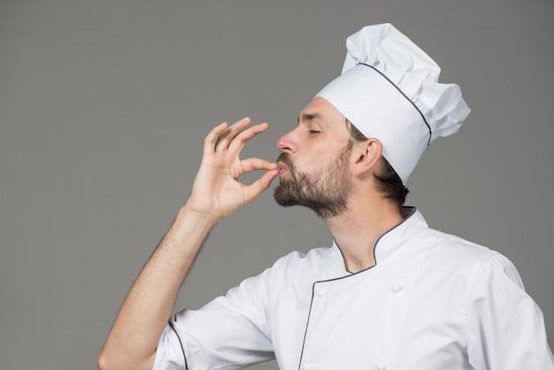 Berufschefmann, der zeichen für köstliches zeigt
