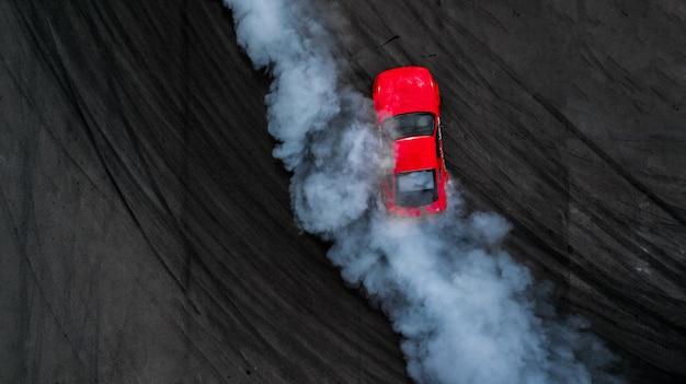 Berufsfahrer-driftauto der luftaufsicht auf asphaltbahn mit rauche, ansicht vom oben genannten autotrieb.