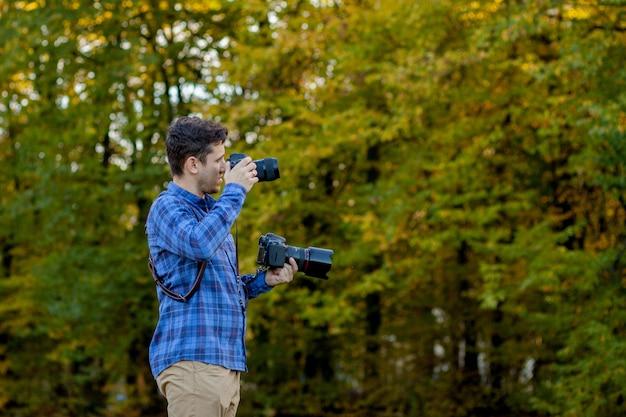 Berufsfotograf in der aktion mit zwei kameras auf schultergurten