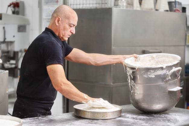 Berufsgebäck chef, der sahne im großen kasserolle an der konditoreiküche wischt.