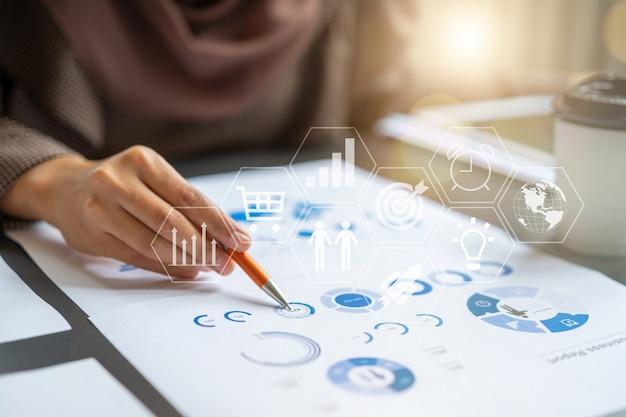 Berufsgeschäftsfrau, die im finanzinvestitionsprojektdiagramm-diagrammbericht überprüft