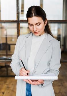 Berufsgeschäftsfrauschreiben auf tagebuch