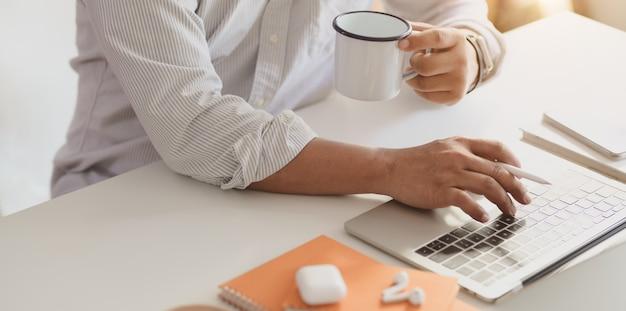 Berufsgeschäftsmann, der auf laptop-computer beim trinken eines tasse kaffees schreibt
